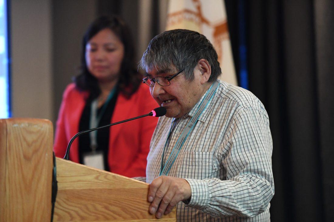 Elderly man speaking at a podium